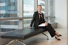 坐在办公室大厅的女实业家 免版税库存照片