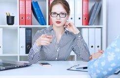 坐在办公室工作场所和指向与一个手指的美丽的体贴的女商人秘密审议 我们寻找 图库摄影