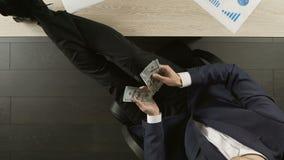 坐在办公室桌上和计数美元,成功的满意的商人 影视素材