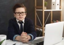 坐在办公室桌上的严肃的小男孩 免版税库存照片