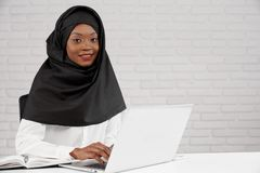 坐在办公室桌上的hijab的妇女,使用膝上型计算机 免版税库存图片