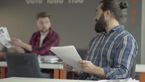 坐在办公室的两个同事学习从纸的新的运作的信息 请求的年轻人在背景中忠告 股票录像
