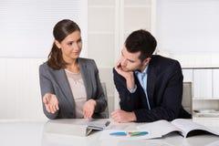 坐在办公室的两个商人谈话和分析 免版税图库摄影