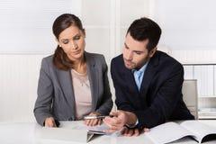 坐在办公室的两个商人谈话和分析 库存图片