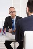 坐在办公室的两个商人:会议或工作面试 免版税库存照片