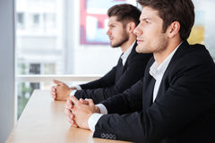 坐在办公室的两个确信的年轻商人 免版税库存照片