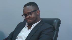 坐在办公室的周道的非裔美国人的商人 免版税库存图片