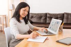坐在办公室的宜人的亚洲妇女 免版税库存照片