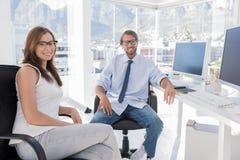 坐在办公室的对设计师 免版税库存照片