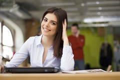 坐在办公室的少妇 免版税库存图片