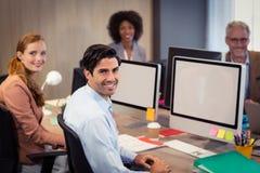坐在办公室的微笑的商人 免版税库存照片