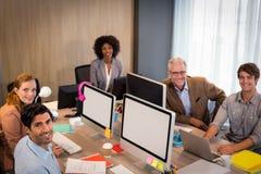 坐在办公室的微笑的商人 库存图片