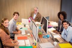 坐在办公室的微笑的商人 免版税库存图片