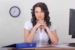 坐在办公室的性感的女实业家 免版税库存图片