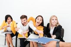 坐在办公室的情感同事设法得到文件夹 免版税库存照片