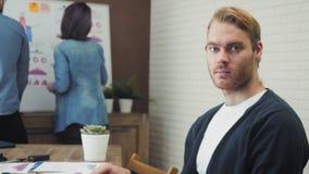 坐在办公室的愉快的妇女画象运作在他的便携式计算机 股票录像