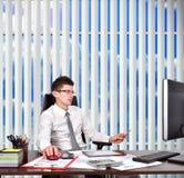 坐在办公室的生意人 免版税库存图片