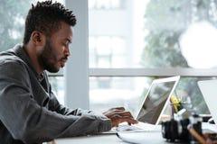 坐在办公室的英俊的想法的严肃的年轻人coworking 免版税库存图片