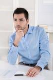 坐在办公室的英俊的年轻经理考虑sens 免版税库存照片