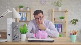 坐在办公室的衬衣和玻璃的年轻人困惑看存钱罐 股票视频