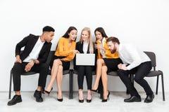 坐在办公室的被集中的同事使用便携式计算机 图库摄影