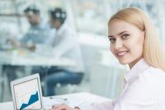 坐在办公室的年轻女实业家 免版税库存照片