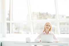 坐在办公室的年轻女实业家 图库摄影