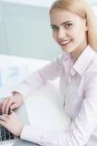 坐在办公室的年轻女实业家 免版税图库摄影