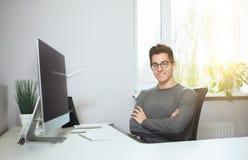 坐在办公室的年轻工人在计算机 一件白色衬衣和玻璃的自由职业者 设计师在前面坐 库存图片