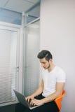 坐在办公室的年轻工人在计算机 一件白色衬衣的自由职业者 设计师在工作场所坐 免版税库存图片