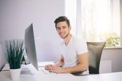 坐在办公室的年轻工人在计算机 一件白色衬衣的自由职业者 设计师在窗口前面参加  库存图片