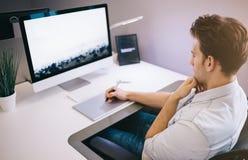 坐在办公室的年轻工人在计算机 一件蓝色衬衣的自由职业者 设计师在窗口前面参加  库存图片