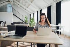 坐在办公室的年轻快乐的夫人照片coworking,当使用聊天由电话时的便携式计算机 看 免版税库存照片