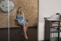 坐在办公室门道入口的少妇 库存照片