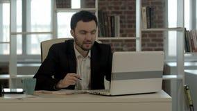 坐在办公室,查寻想法的年轻商人 股票录像