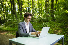 坐在办公桌工作的商人在便携式计算机在绿色森林公园 工作在绿色p的办公室桌上的自由职业者 库存图片