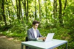 坐在办公桌工作的商人在便携式计算机在绿色森林公园 工作在绿色p的办公室桌上的自由职业者 免版税库存照片