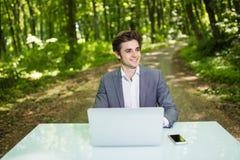 坐在办公桌工作的商人画象在便携式计算机在绿色森林公园 运作的自由职业者画象 库存照片