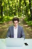 坐在办公桌工作的商人画象在便携式计算机在绿色森林公园 运作的自由职业者画象 免版税图库摄影