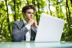 坐在办公桌工作的想法的商人画象在便携式计算机在绿色森林公园 自由职业者用手 免版税库存图片