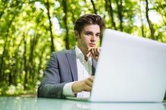 坐在办公桌工作的想法的商人画象在便携式计算机在绿色森林公园 自由职业者用手 库存照片