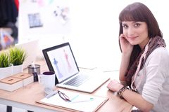 坐在办公桌的可爱的女性时装设计师画象  女性时装设计师 免版税库存图片