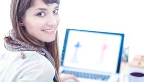 坐在办公桌的可爱的女性时装设计师画象  库存照片