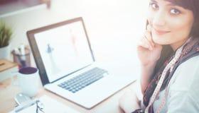 坐在办公桌的可爱的女性时装设计师画象  免版税库存图片