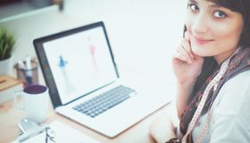 坐在办公桌的可爱的女性时装设计师画象  库存图片