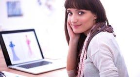 坐在办公桌的可爱的女性时装设计师画象  免版税库存照片