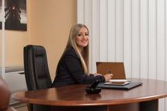 坐在办公桌的女实业家签合同 库存照片