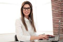 坐在办公桌的微笑的女商人 免版税库存图片