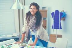 坐在办公桌的微笑的女性时装设计师 免版税库存照片