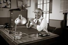 坐在办公桌的微笑的葡萄酒主任 免版税库存照片